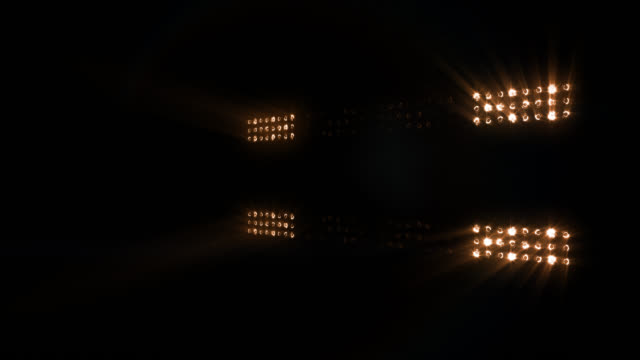 Stage, concert or stadium lights flashing, with sound. Warm colors. video