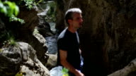 standing on a rock in front of a waterfall in wildlife reserve video