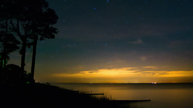 Starlapse with night light on the horizon video