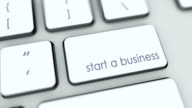 Start a business button on computer keyboard. Key is pressed. User presses keypad with icon symbol, camera pan, different graphics on keyboard available for download. Using computers contemporary technology, browsing internet pushing buttons. video