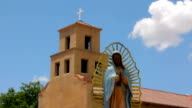 Statue of the Our Lady of Guadalupe Standing Peacefully in front of an Adobe Church video