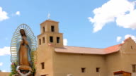 Statue of the Virgin of Guadalupe Stands Serenely in front of an Adobe Church video