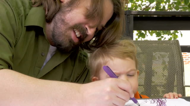 A stay at home dad drawing with his baby boy as he watches intently video