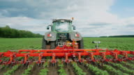 Steadicam fly around shot: Tractor pulls on the field, agricultural mechanism for weeding plants video