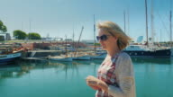 Steadicam shot: A female tourist walks along the docks with yachts. Barcelona, Spain video