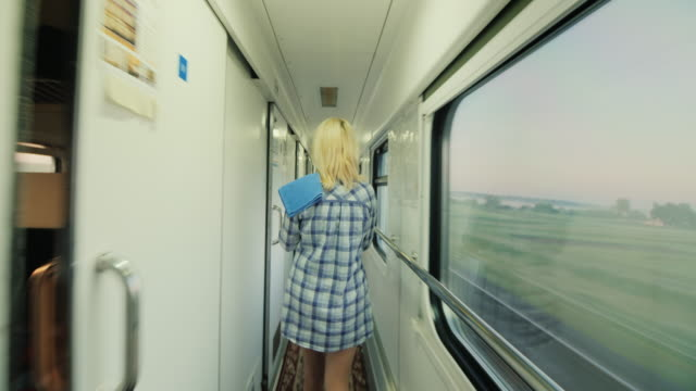 Steadicam shot: A woman with a towel is walking along the train of a passenger train. Early morning on the way. Rear view video