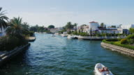 Steadicam shot: channel with the elite real estate. Empuriabrava, Spain, Catalonia. Floats small boat with tourists video
