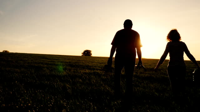 Steadicam shot: Farmers - a man and a woman walking across the field at sunset. Carry a tree seedling, a watering can and a shovel. Concept - work in the garden, volunteering, a new life video