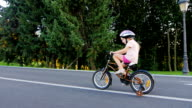 Steadicam shot: Funny girl five years old riding a bicycle with extra wheels smiling video