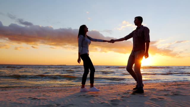 Steadicam shot: Loving couple walking at sunset on the beach or lake. She leads the guy flirting video