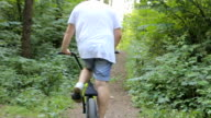 Steadicam shot of bike riding on mountain trail. video