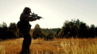 Steadicam shot: Silhouette of armed men, taking aim through the weapon goes ahead video
