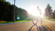Steadicam shot: Silhouette teenager goes on a flat road against the setting sun video