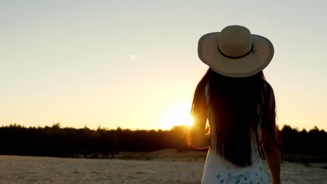 Steadicam shot: Young woman with long hair in a hat. Go towards the setting sun, rear view video