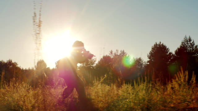 Steadicam slow motion shot: Silhouette of armed men in the attack. Runs with arms in the sun video