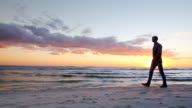 Steadicam slow motion shot: Young lonely man walking along the seashore at sunset video