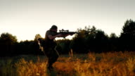Steadicam slowmotion shot: An armed man running in the attack. Holding in hands the weapon, in the setting sun video