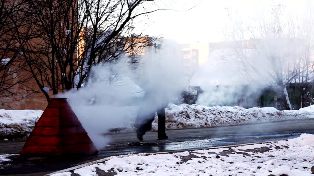 Steam on winter street from water system video