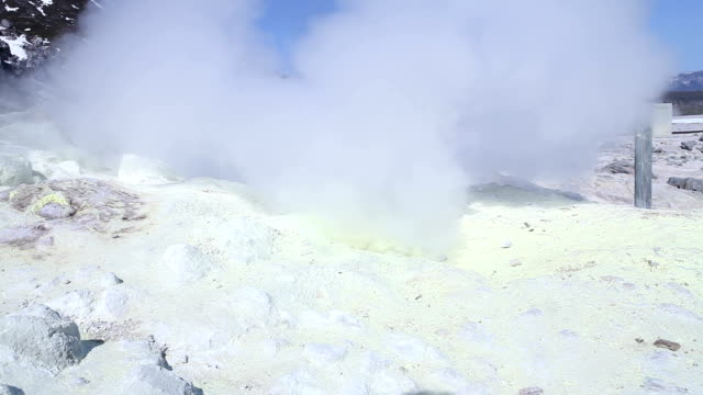Steam rising out of a large suphur vent with mountains in the background - Mid-shot video