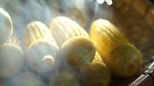 Steamed corn cob in morning sunlight at Asian market video