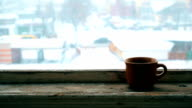 Steaming earthenware cup on old wooden window sill video