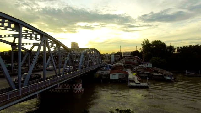 Steel Bridge across River with Morning Sunlight and Golden Sky. Aerial shot video