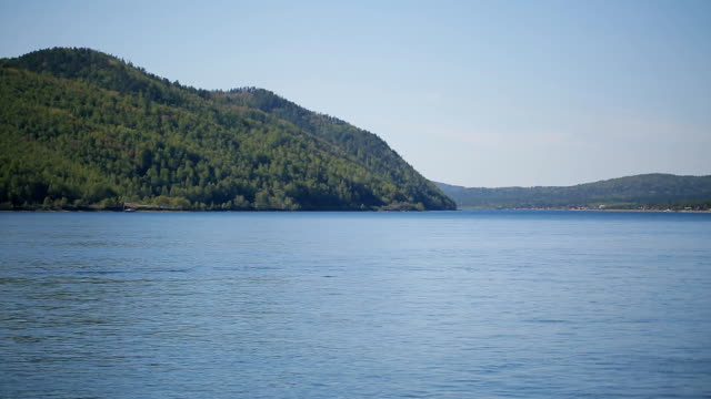 Steep bank of sea or lake with thick forest on a sunny day and blue sky video