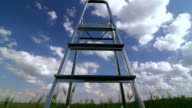 Stepladder in green field against blue sky with clouds video