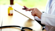 Stethoscope with doctor using tablet PC in medical clinic video