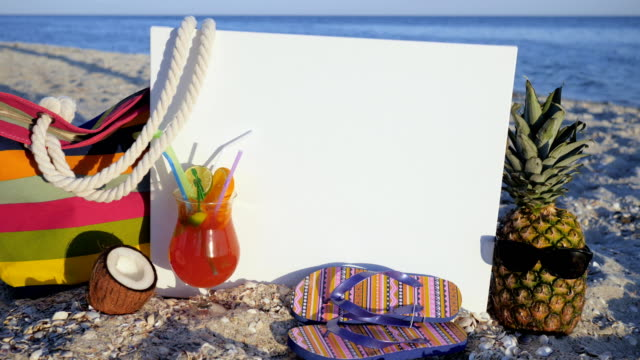 Still life beach, White background for inscription is standing on sand, sea and beach, cocktail with tropical fruits, pineapple video
