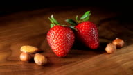 Still life macro with two strawberries and nuts video