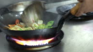 stir fry meal being prepared in a restaurant kitchen flambe style. video