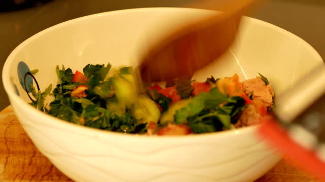 Stiring vegetable lettuce with tuna salad in a bowl video