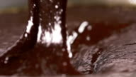 Stirring delicious melted chocolate with a spoon in slow motion video