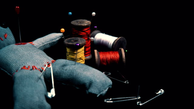 stitched voodoo doll for ritual on a black background with threads and needles video
