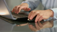 Stock exchange broker works on laptop, inserting data, scrolling video