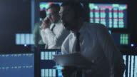 Stockbroker in white shirt is talking on the phone while working in a dark monitoring room with display screens. video