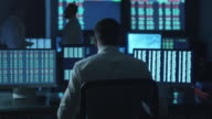 Stockbroker spotted a positive trend in trading charts while working in a dark monitoring room with display screens. video