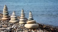 Stone stack on pebble seacoast, waving sea in background video