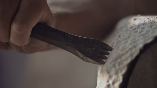 Stonemason carving stone with hammer and chisel video
