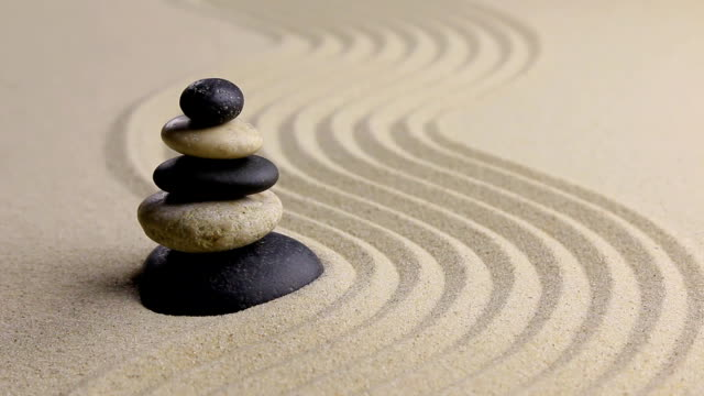 Stones pyramid on sand symbolizing zen, harmony, balance,motion, video