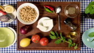 Stop motion: making chickpea salad with feta onion tomatoes herbs video