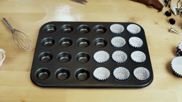 Stop motion. Paper cups, wrappers for cupcakes putting into the baking tray for muffins. Cooking in the kitchen video