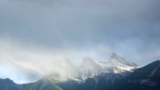 Storm clouds swirl around mountain peaks video