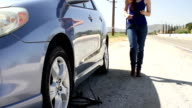 Stranded Driver Hispanic Woman Changes Tire Trackleft video