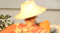 Straw doll with farmer hat stand against wind video