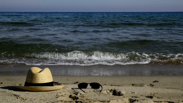 straw hat and sunglasses on the sand. video