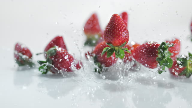 SLO MO LD Strawberries bouncing off water covered surface video