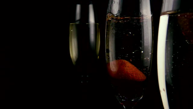 Strawberries fall into a glass with champagne. Slow motion video