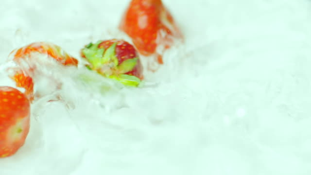 Strawberries fall into the water video